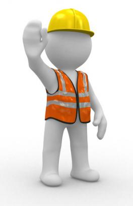An individual wearing a hard hat and reflectve vest is holding up a hand gesturing to stop