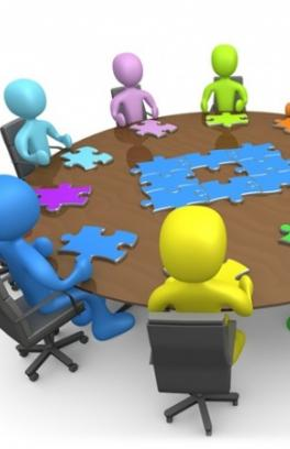 individuals sitting around a round table at a meeting with a puzzle in the center of the table. Each individual has in front of them a puzzle piece.