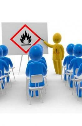 A classroom of people with an instructor pointing to a presention. The presentation is showing a hazard symbol.