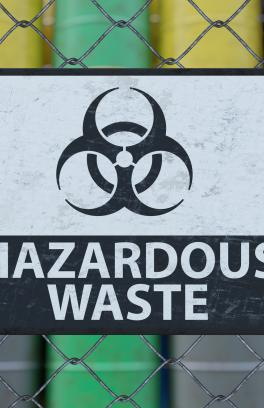 A sign on a fence with a hazard symbol and the words Hazardous Waste