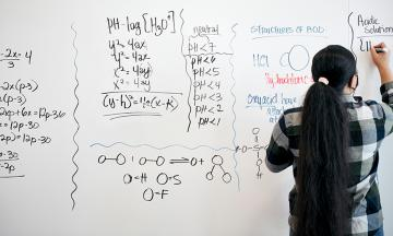 A woman performs calculations on a whiteboard
