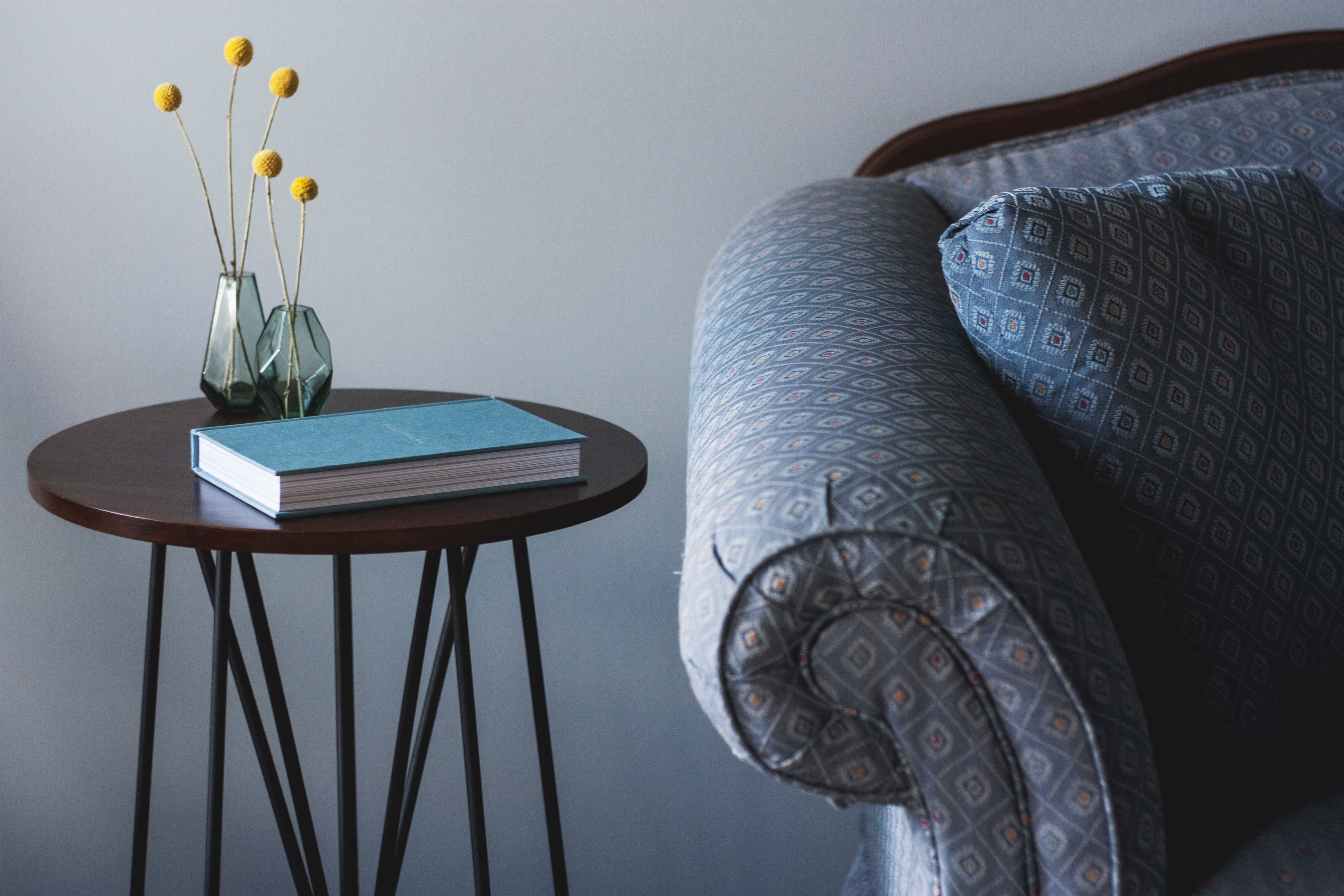 This photo is decorative. A blue chair and side table with a notebook.