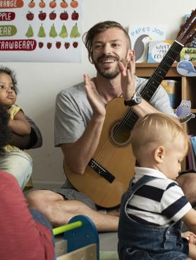 Teacher playing guitar with children