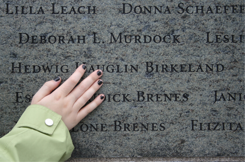 Close up of hand touching engraved names on stone wall
