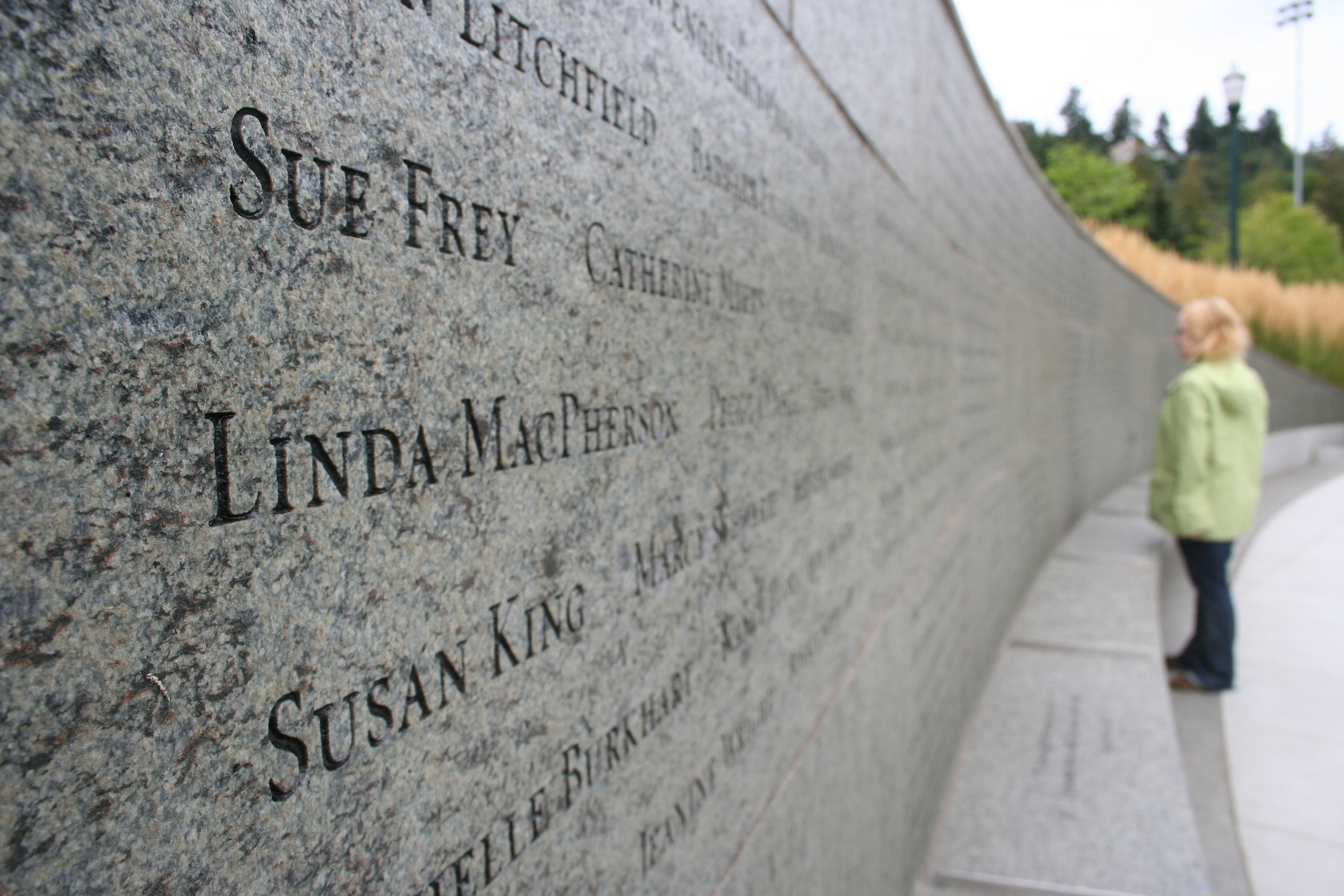 Close up of stone wall with engraved names and woman in background