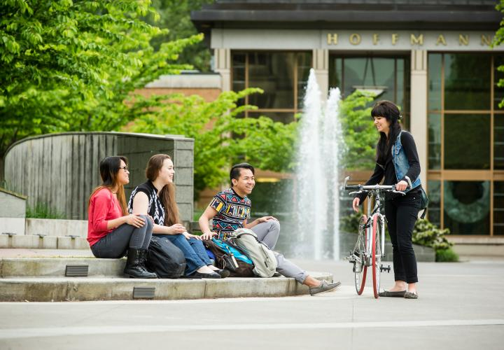 Group of four students, three sitting on steps of stage and one standing with bike
