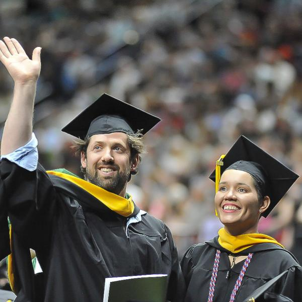 man and woman in cap and gown at commencement
