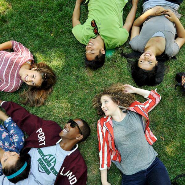 diverse students laying on grass in Park Blocks