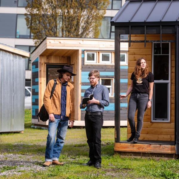 PSU faculty and students in front of tiny homes for people experiencing homelessness