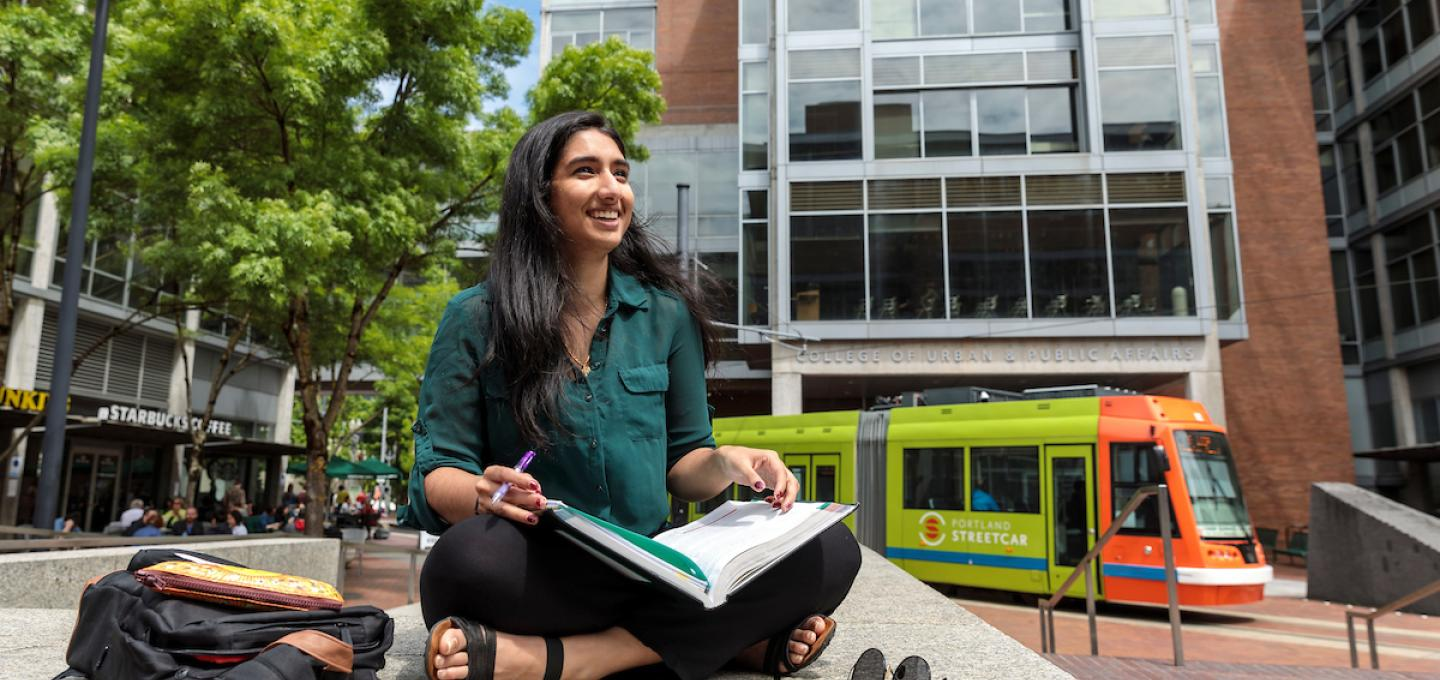 Student Studying outside in summer while streetcar goes by