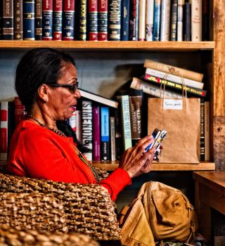 Older woman with cell phone and bookshelf