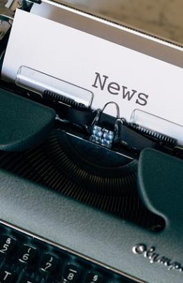 "Typewriter with paper on the roller that says ""News"""