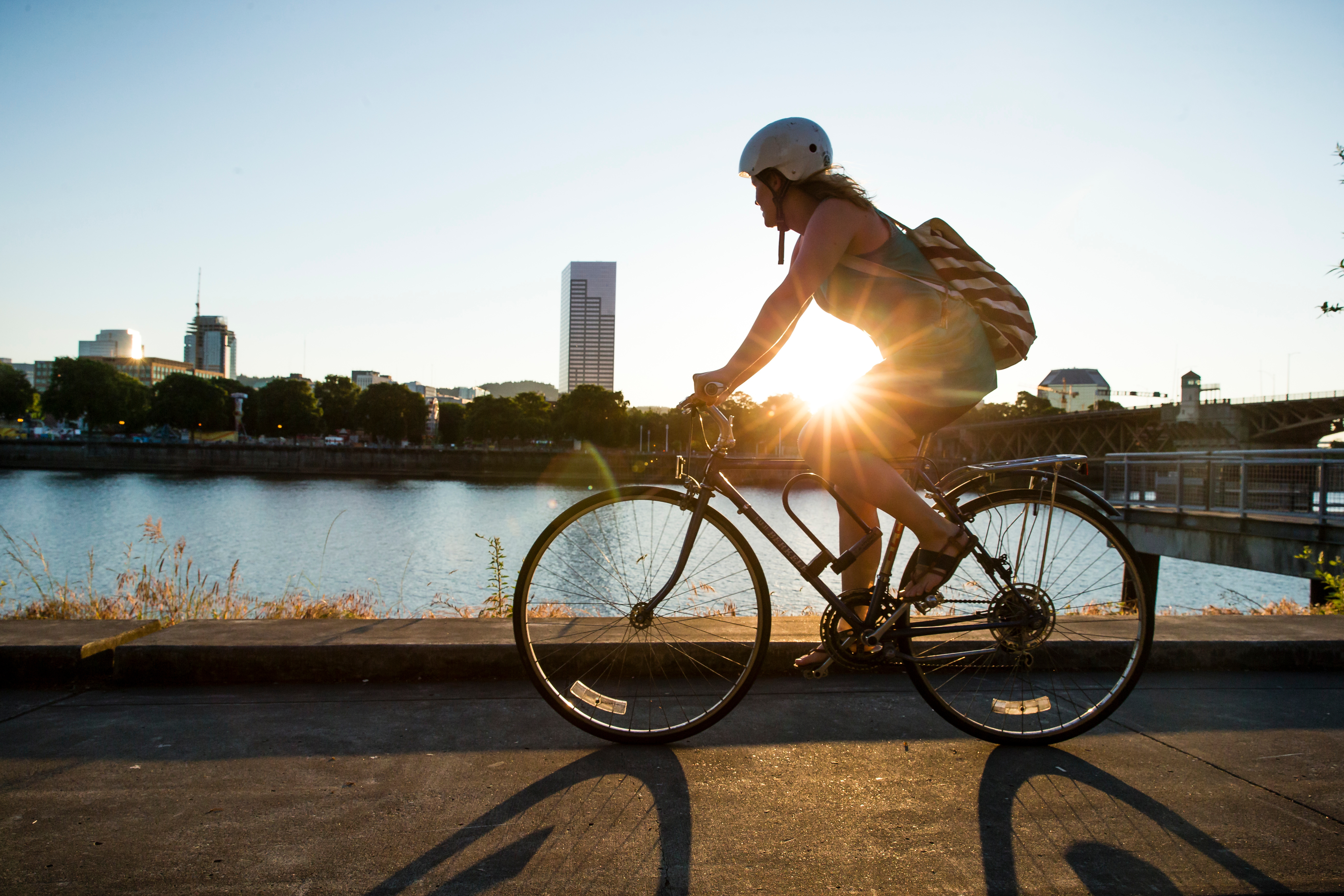 Person cycling by a river with the sun setting on the other side of them.