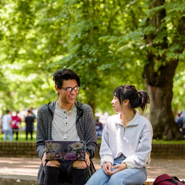 Two students sitting in front of many leafy green trees. One has a laptop.