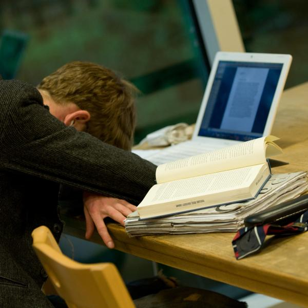 Photo of a student with his head on the desk on front of his laptop resting from study exhaustion
