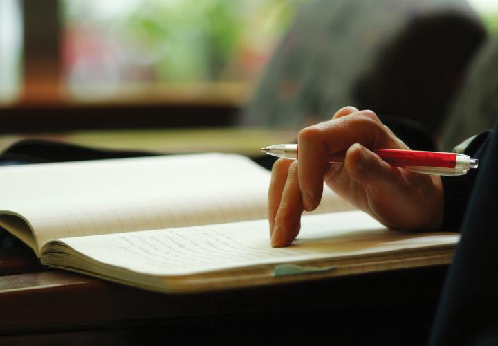 Hand holding a pen and resting on an open notebook.