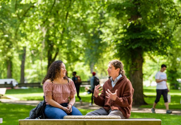 Photo of two students on a bench in the park blocks have a conversation