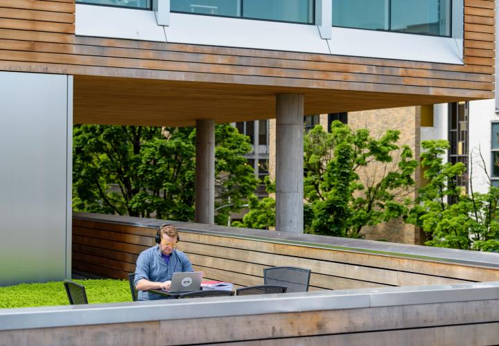 Photo of a student sitting outside on the green roof of the Karl Miller Center on his laptop and headphones doing homework all alone.