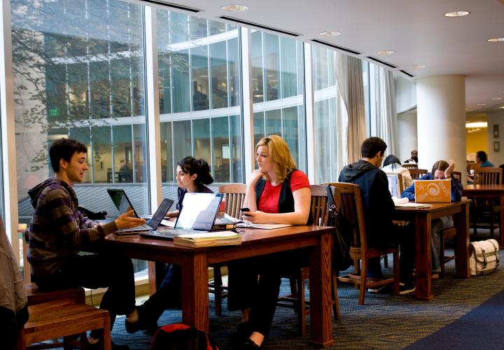 Students sitting together at a table in Millar Library all with laptops open.