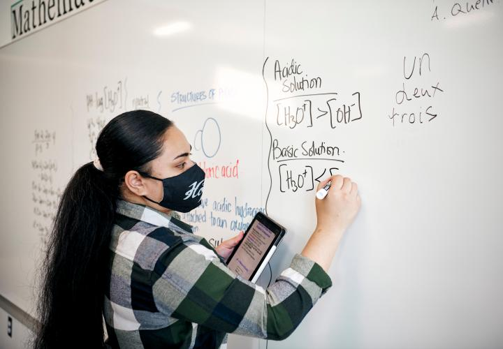 PSU student with light skin and long dark hair pulled back in a ponytail. They're using a whiteboard to work on an equation. They have on a black face mask with white writing and a green, white, and black plaid long sleeve shirt.