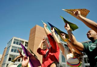 Group of students holding multicolored paper airplanes in the air.