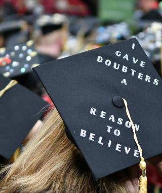 Back of head photo of a students wearing a mortar board on graduation day.