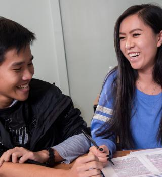 A tutor and student laughing and smiling while working