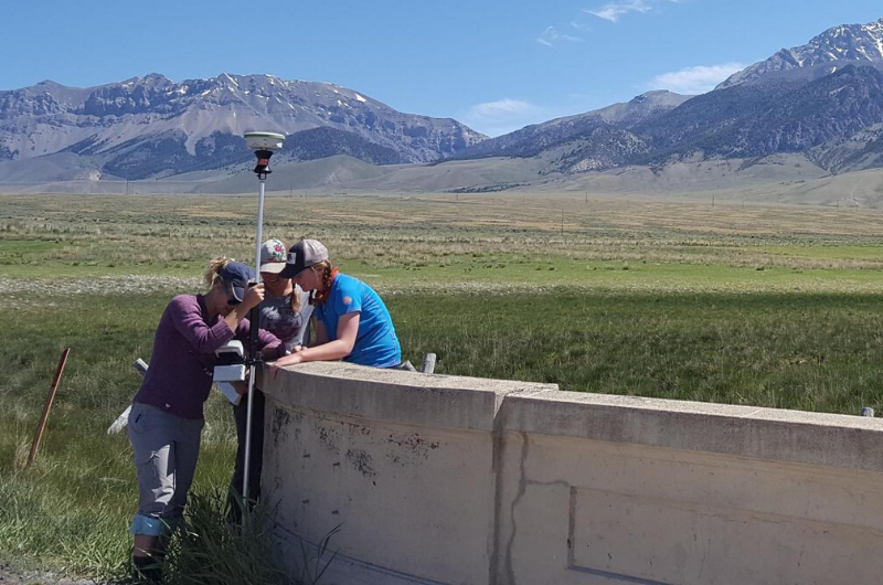Three students taking measurements with mountains in background