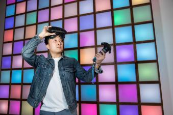 PSU Computer Modeling and Simulation Graduate Man in jean jacket with virtual reality headset and colorful square background