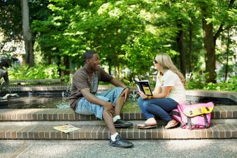 two Portland State University graduate creative writing students studying in a park