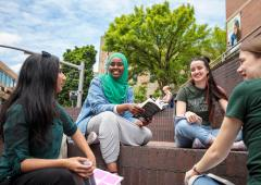 Group of four students sitting in Urban Plaza in conversation