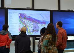 Group of people looking at map displayed on projector