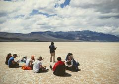 Group of students seated at natural area, with mountains in backdrop