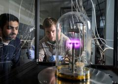 Two students looking at science equipment in lab