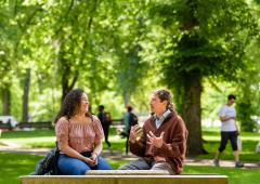 Man, woman seated on bench in conversation
