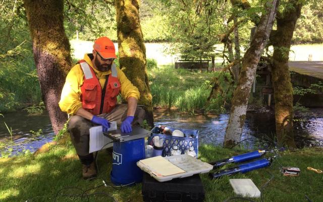 USGS hydrologist sitting by a body of water with a laptop and other scientific instruments
