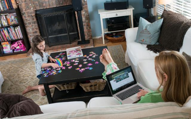 Mom on couch with laptop, daughter playing with puzzle at coffee table