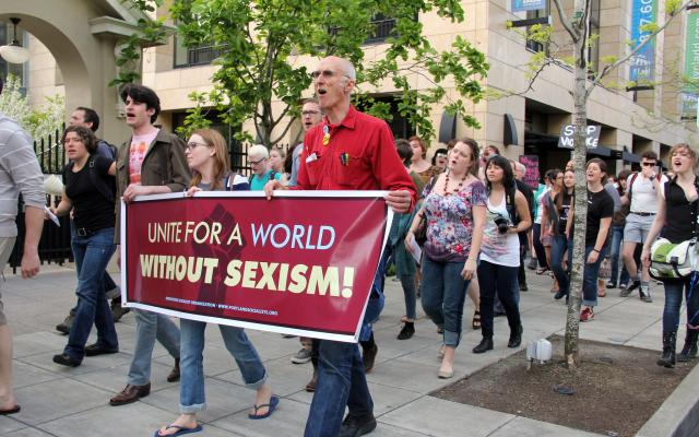 "Group of people marching with sign that reads, ""Unite for a World Without Sexism"""