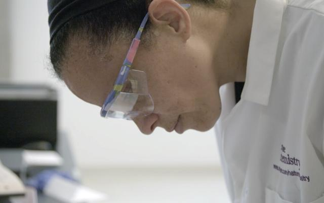 Scientist in lab coat and safety goggles looking down