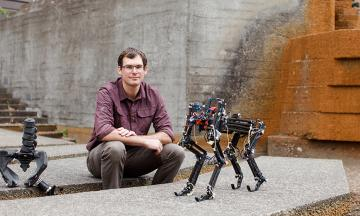 Alex hunt poses with two robots