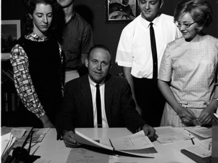 A black and white scene of a man in a suit and tie sits desk surrounded by four students all in 1960s attire.
