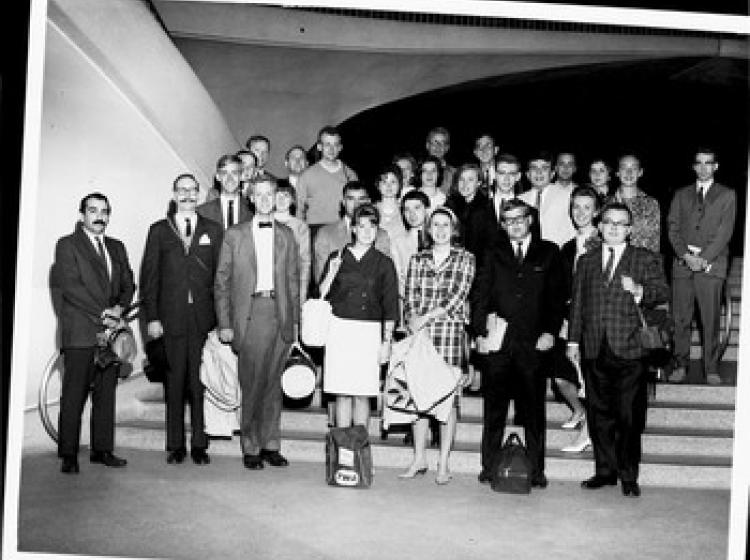 A black and white photo of students on a staircase in 1960s attire.