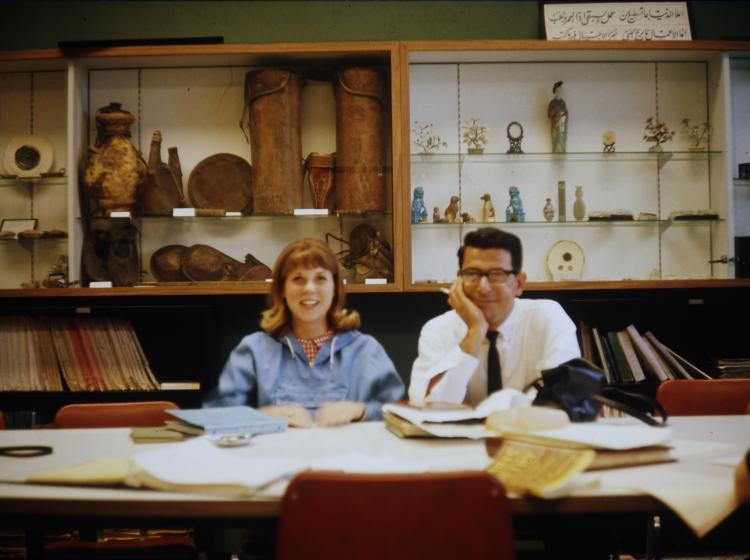 A woman and a man are sitting at a table covered in books and papers with historical artifacts on display in the background.