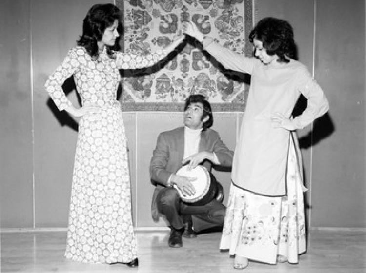 Two women dance in front of a man kneeling with a drum in rehearsal for Persian New Year event at PSU, 1972.