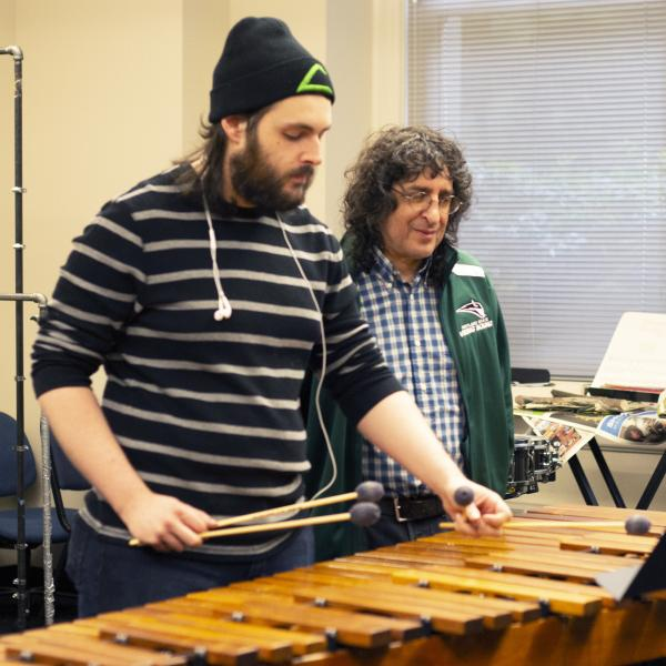 Percussion student and instructor in rehearsal