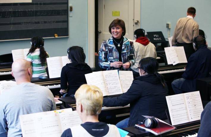 Instructor teaching piano students