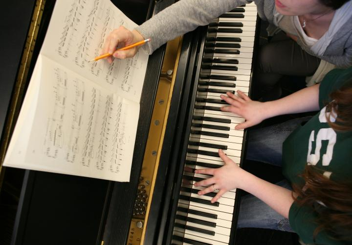 Instructor and student edit a score at the piano