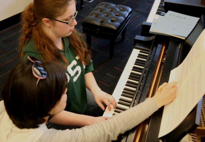 Piano student and teacher in private lesson