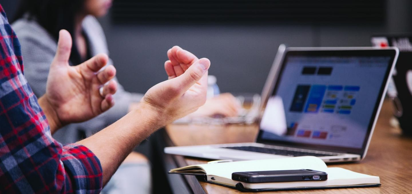 hands making gestures in front of a laptop