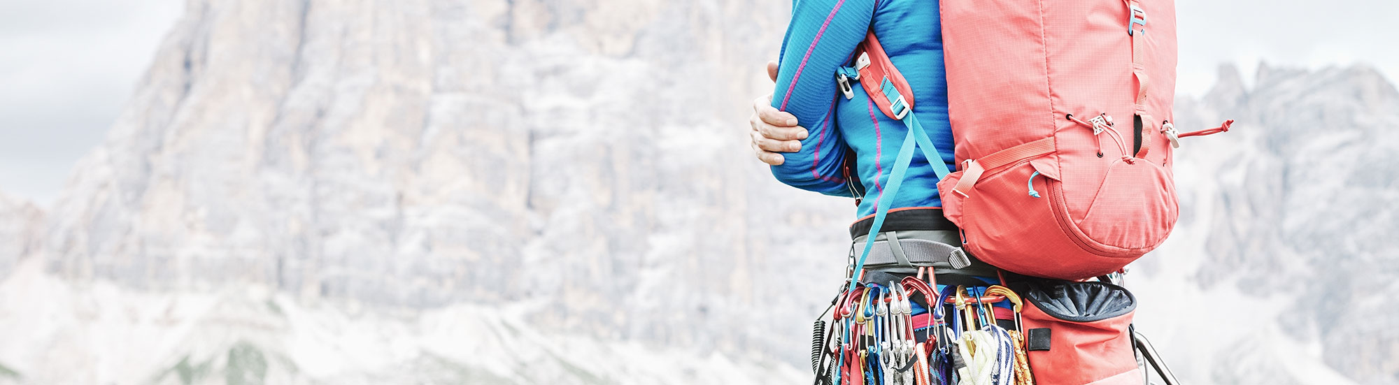 A rock climber in professional gear looking at a mountain